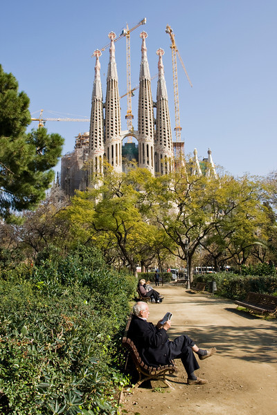 Man on bench in front of the Sagrada Familia in Barcelona