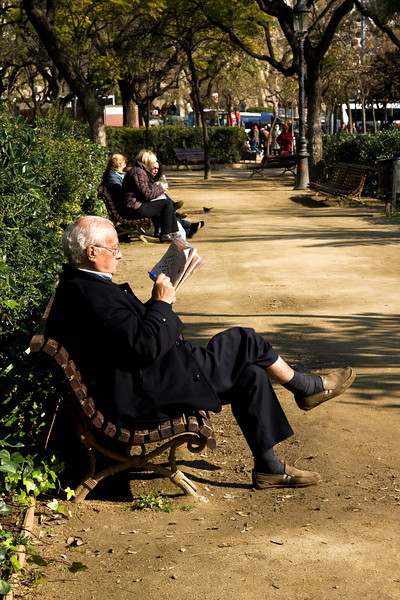 Spanish man doing a crossword in the park