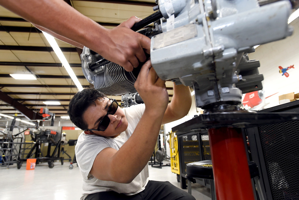 . Ryan Alpeche, center, and Mark Acker, left, work to reassemble a reciprocating engine at the Spartan College of Aeronautics on Wednesday in Broomfield. For more photos of the course activity go to dailycamera.com Jeremy Papasso/ Staff Photographer 06/06/2018