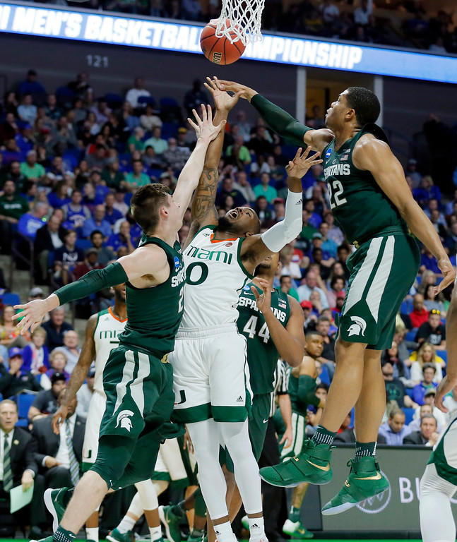 . Michigan State guard Matt McQuaid, left, and Miles Bridges (22), combine to block a shot by Miami guard Ja\'Quan Newton (0) in the first half of a first-round game in the men\'s NCAA college basketball tournament in Tulsa, Okla., Friday March 17, 2017. (AP Photo/Tony Gutierrez)