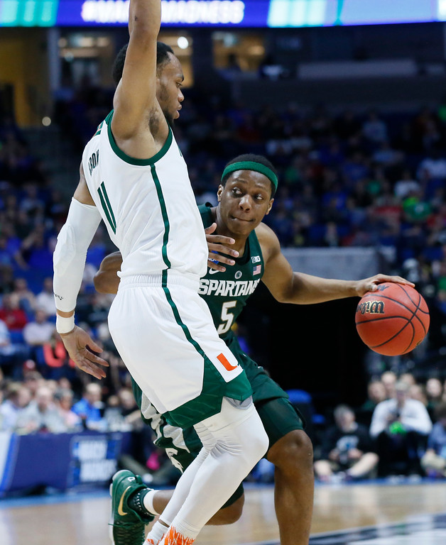 . Michigan State\'s Cassius Winston (5) drives around Miami\'s Bruce Brown (11) in the first half of a first-round game in the men\'s NCAA college basketball tournament in Tulsa, Okla., Friday, March 17, 2017. (AP Photo/Sue Ogrocki)