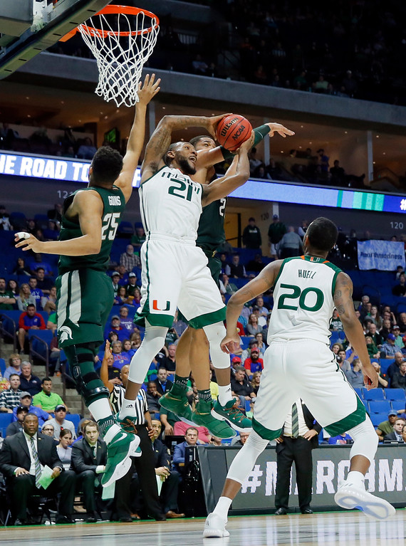 . Miami forward Kamari Murphy (21) comes down with a rebound in front of Michigan State forward Kenny Goins (25) and Miles Bridges, rear, in the second half of a first-round game in the men\'s NCAA college basketball tournament in Tulsa, Okla., Friday March 17, 2017. (AP Photo/Tony Gutierrez)