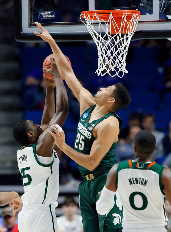 . Miami center Ebuka Izundu (15) has his shot blocked by Michigan State forward Kenny Goins (25) as Ja\'Quan Newton (0) watches in the second half of a first-round game in the men\'s NCAA college basketball tournament in Tulsa, Okla., Friday March 17, 2017. (AP Photo/Tony Gutierrez)