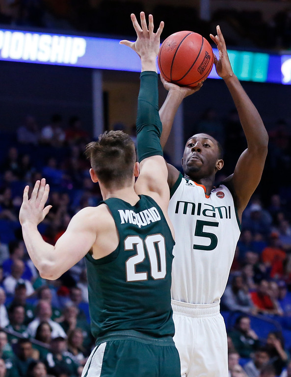 . Miami\'s Davon Reed shoots over Michigan State\'s Matt McQuaid (20) in the second half of a first-round game in the men\'s NCAA college basketball tournament in Tulsa, Okla., Friday, March 17, 2017. Michigan State won 78-58. (AP Photo/Sue Ogrocki)