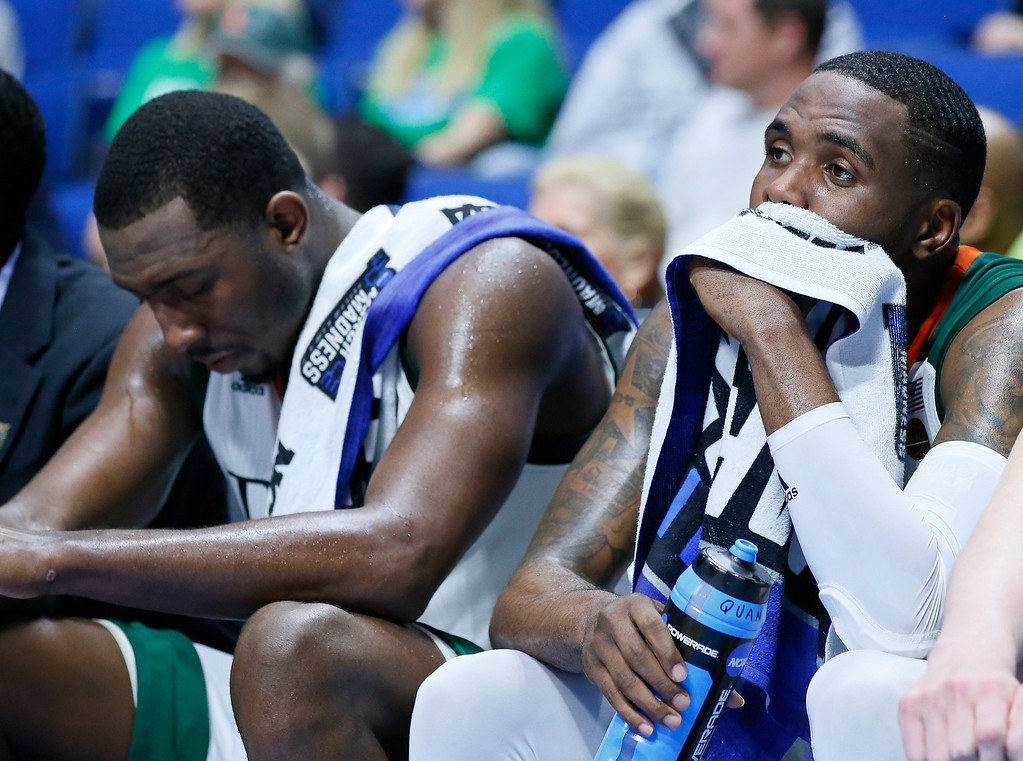 . Miami\'s Ja\'Quan Newton, right, and Davon Reed, left, sit on the bench late in the second half of a first-round game against Michigan State in the men\'s NCAA college basketball tournament in Tulsa, Okla., Friday, March 17, 2017. Michigan State won 78-58. (AP Photo/Sue Ogrocki)