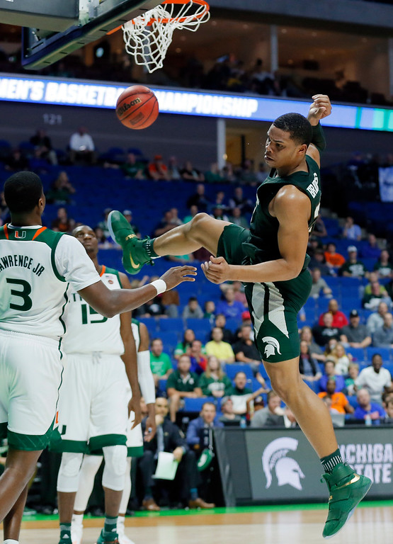 . Miami forward Anthony Lawrence Jr. (3) and Ebuka Izundu (15) watch as Michigan State guard Miles Bridges (22) recovers after dunking the ball late in the second half of a first-round game in the men\'s NCAA college basketball tournament in Tulsa, Okla., Friday March 17, 2017. (AP Photo/Tony Gutierrez)