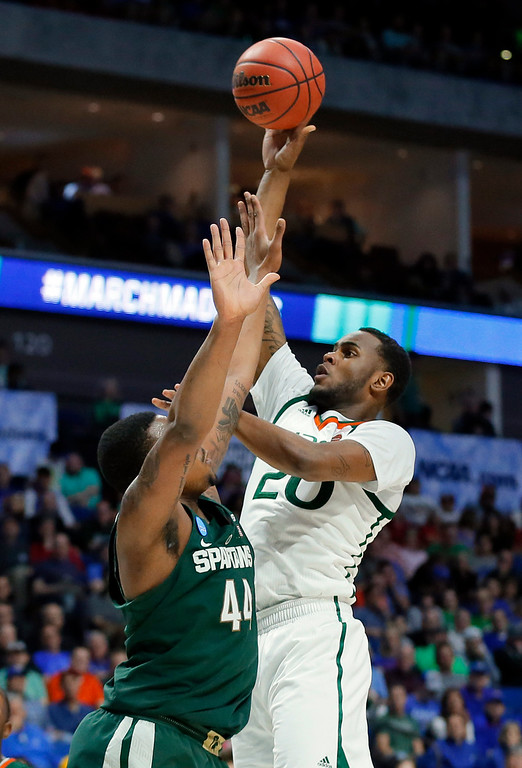 . Michigan State forward Nick Ward (44) defends as Miami forward Dewan Huell (20) takes a shot in the first half of a first-round game in the men\'s NCAA college basketball tournament in Tulsa, Okla., Friday March 17, 2017. (AP Photo/Tony Gutierrez)
