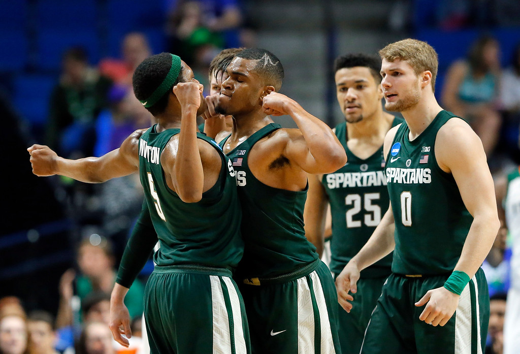 . Michigan State guard Cassius Winston (5) and guard Alvin Ellis III, center, celebrate a basket as Kenny Goins (25) and Kyle Ahrens (0) watch in the first half of a first-round game in the men\'s NCAA college basketball tournament against Miami in Tulsa, Okla., Friday March 17, 2017. (AP Photo/Tony Gutierrez)