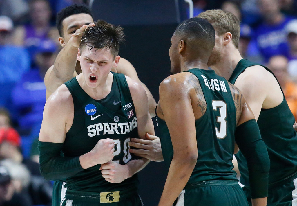 . Michigan State\'s Matt McQuaid, center, celebrates with teammates Kenny Goins, left, and Alvin Ellis III, right, in the first half of a first-round game against Miami in the men\'s NCAA college basketball tournament in Tulsa, Okla., Friday, March 17, 2017. (AP Photo/Sue Ogrocki)
