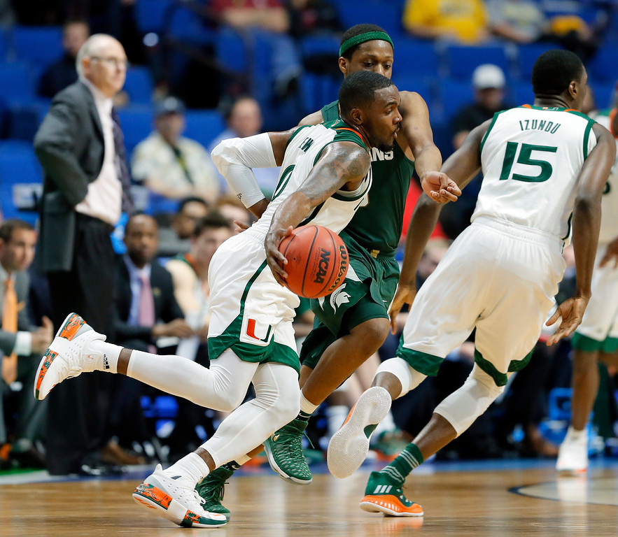 . Miami guard Ja\'Quan Newton (0) advances the ball as Michigan State guard Cassius Winston, defends in the second half of a first-round game in the men\'s NCAA college basketball tournament in Tulsa, Okla., Friday March 17, 2017. (AP Photo/Tony Gutierrez)