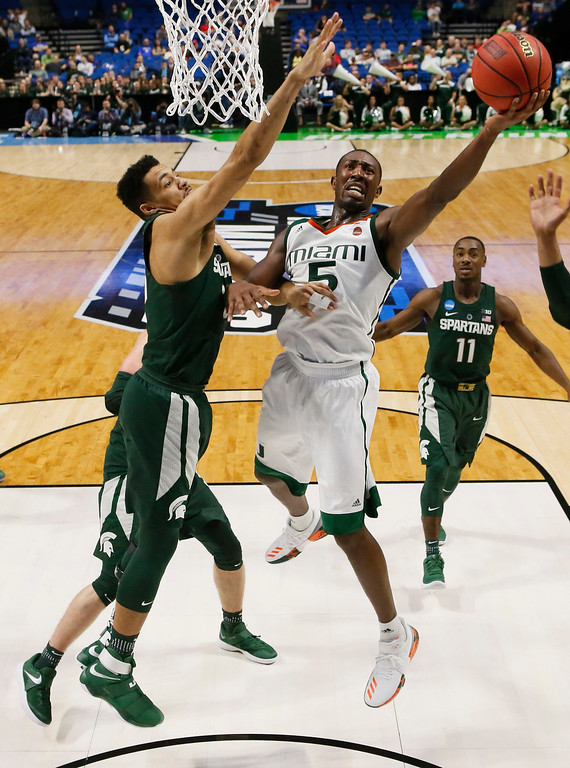 . Miami\'s Davon Reed (5) shoots in front of Michigan State\'s Kenny Goins, left, in the second half of a first-round game in the men\'s NCAA college basketball tournament in Tulsa, Okla., Friday, March 17, 2017. Michigan State won 78-58. (AP Photo/Sue Ogrocki)