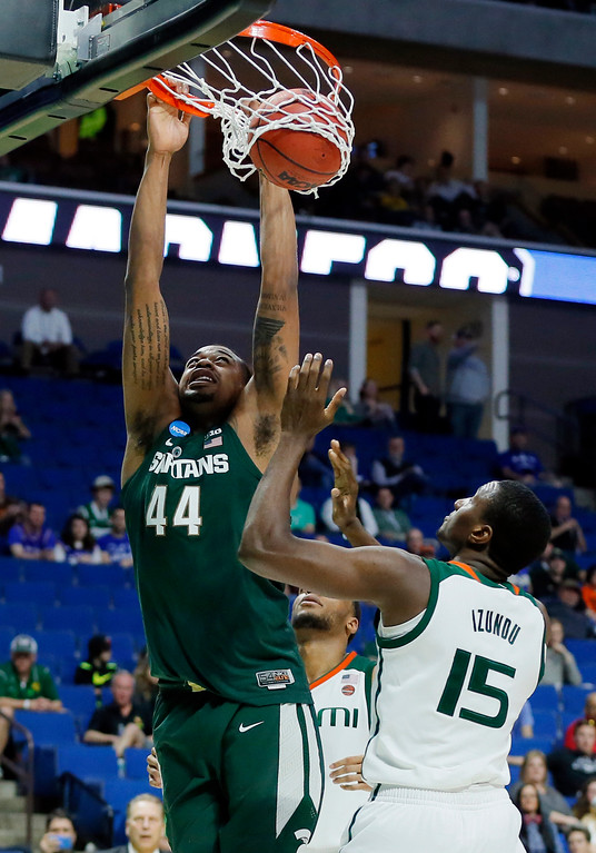 . Michigan State forward Nick Ward (44) hangs on to the rim after dunking the ball as Miami center Ebuka Izundu (15) watches in the second half of a first-round game in the men\'s NCAA college basketball tournament in Tulsa, Okla., Friday March 17, 2017. (AP Photo/Tony Gutierrez)