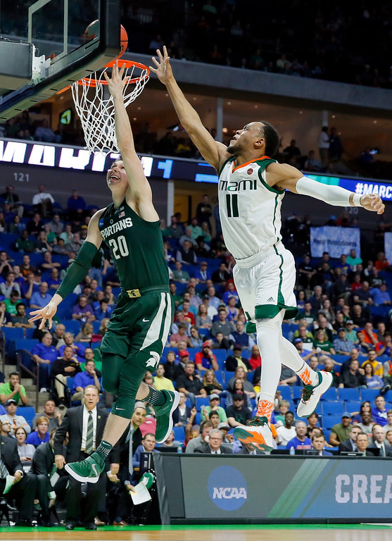. Michigan State guard Matt McQuaid (20) goes up for a shot after getting past Miami guard Bruce Brown (11) in the second half of a first-round game in the men\'s NCAA college basketball tournament in Tulsa, Okla., Friday March 17, 2017. (AP Photo/Tony Gutierrez)