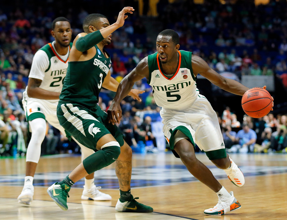 . Michigan State guard Alvin Ellis III (3) defends as Miami guard Davon Reed (5) moves to the basket in the first half of a first-round game in the men\'s NCAA college basketball tournament in Tulsa, Okla., Friday March 17, 2017. (AP Photo/Tony Gutierrez)