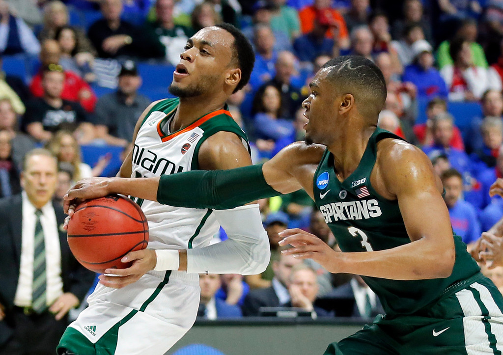. Miami guard Ja\'Quan Newton, left, works to get a shot off against Michigan State guard Alvin Ellis III (3) in the first half of a first-round game in the men\'s NCAA college basketball tournament in Tulsa, Okla., Friday March 17, 2017. (AP Photo/Tony Gutierrez)