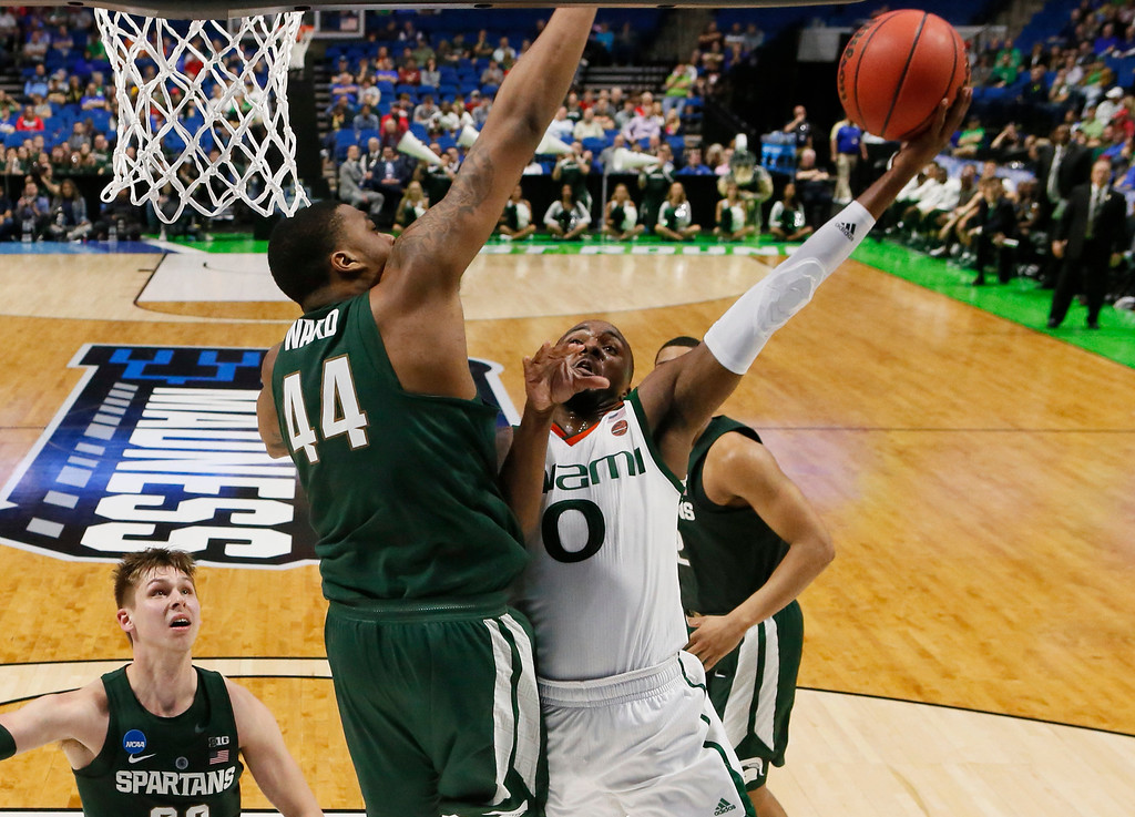 . Miami\'s Ja\'Quan Newton (0) shoots in front of Michigan State\'s Nick Ward (44) in the second half of a first-round game in the men\'s NCAA college basketball tournament in Tulsa, Okla., Friday, March 17, 2017. Michigan State won 78-58. (AP Photo/Sue Ogrocki)