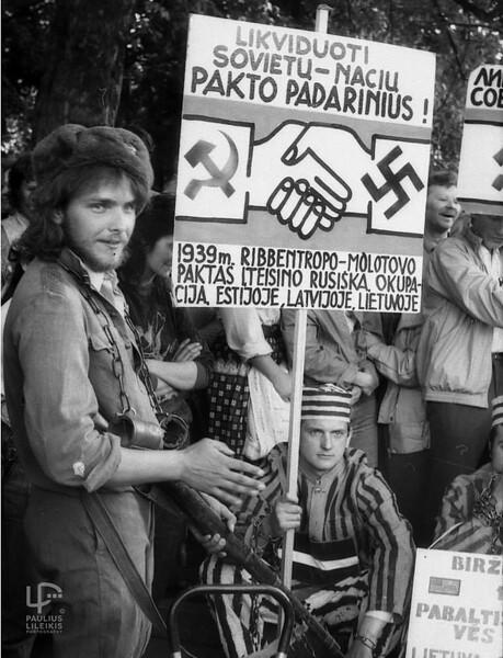 Stovi žurnalistas Gintaras Mikšiūnas, sėdi su plakatu Stanislovas Buškevičius.
