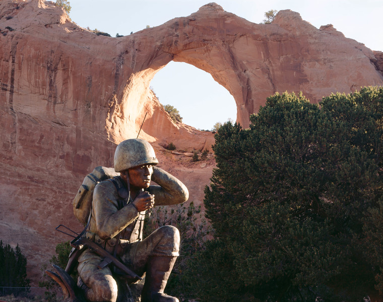 Window Rock, with a sculpture of a Navajo Code Talker in the foreground, at dawn.
