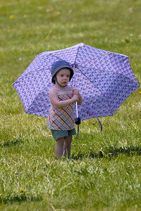 Stock image of young girl holding an umbrella at the International Kite and Culture Festival in Georgetown Kentucky USA