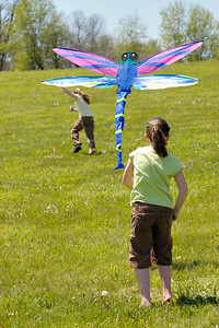 Stock image of two young girls with their colorful dragonfly kite at the International Kite and Culture Festival in Georgetown Kentucky USA