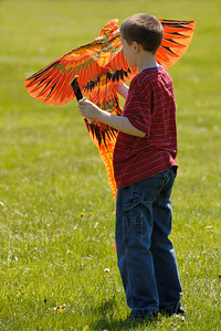 Stock image of young boy with his orange kite at the International Kite and Culture Festival in Georgetown Kentucky USA