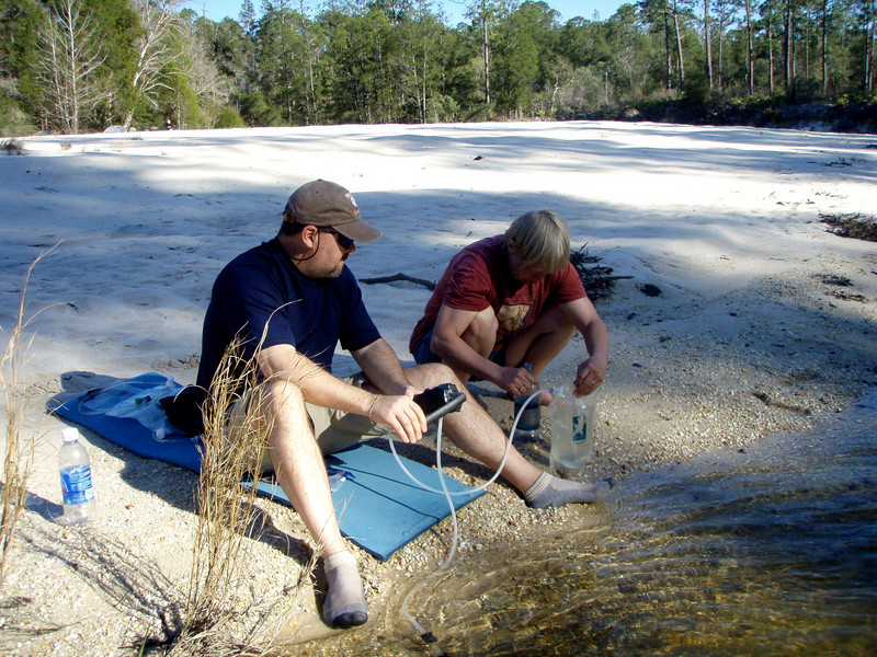 Jeff pumps water while Bumpkin lends a hand.