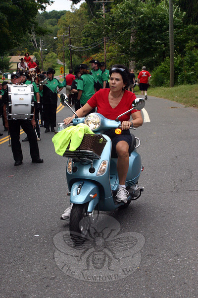 Parade Committee President Beth Caldwell was able to move up and down the parade route while saving some of her energy this year thanks to the use of a powder blue Vespa scooter.   (Bee Photo, Hicks)