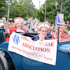 Visiting Nurse Association member Mae Schmidle waves to the crowd at this year's Newtown Labor Day Parade from the back of an antique car. Dan Amaral is behind the wheel, with Sally Schwerdtle next to him. (Bobowick photo)