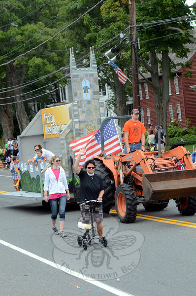 Trinity Episcopal Church members rode or accompanied their float in the Labor Day parade, along with the Reverend Kathleen Adams-Shepherd, who zipped along on a scooter supporting her injured leg. (Voket photo)
