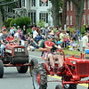 Two generations of local farmers ride their tractor during the finale of the Newtown Labor Day Parade September 3. (Voket photo)