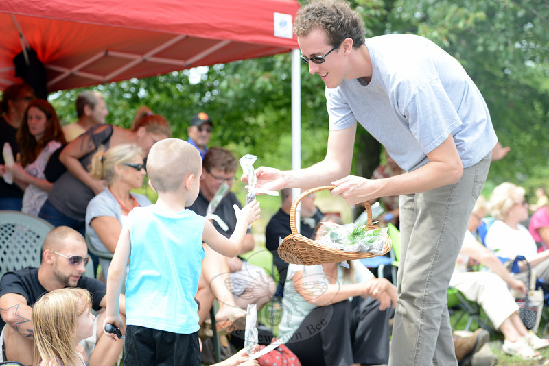 Newtown Forest Association member Aaron Coopersmith hands out sapling trees along the Newtown Labor Day Parade route Monday, September 3. (Bobowick photo)