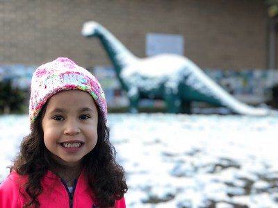 Stella Salas, PK student at Lone Star, with Sinclair the Dinosaur on our snowy day!