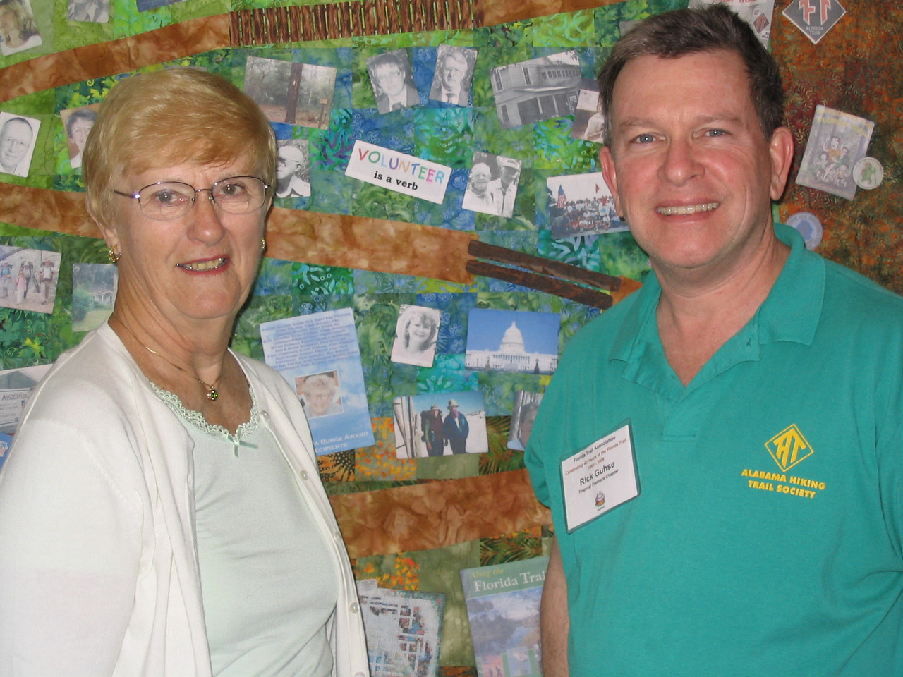 Joan Hobson and Rick Gushe flank their thru-hike photo on the 40th Anniversary quilt<br /> PHOTO CREDIT: Diane Wilkins / Florida Trail Association
