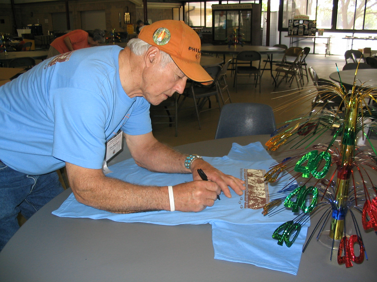 FTA past president Tom Montoya signs a commemorative t-shirt for the auction.<br /> PHOTO CREDIT: Diane Wilkins / Florida Trail Association