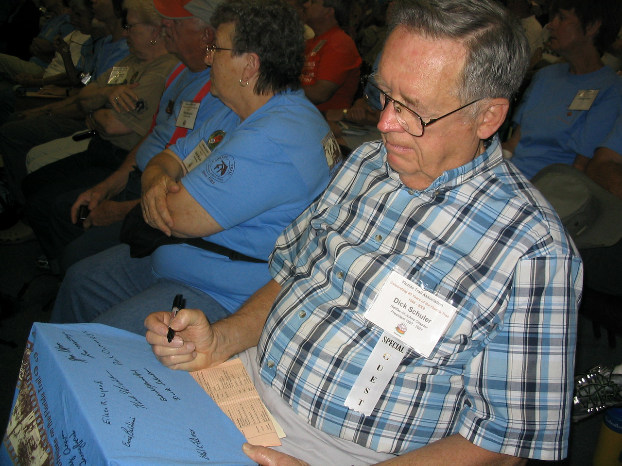 FTA past president Dick Schuler signs a commemorative t-shirt for the auction.<br /> PHOTO CREDIT: Diane Wilkins / Florida Trail Association