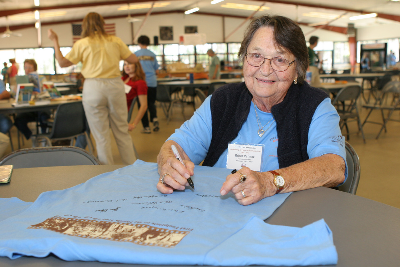 FTA past president Ethel Palmer signs a commemorative t-shirt for the auction.<br /> PHOTO CREDIT: Diane Wilkins / Florida Trail Association