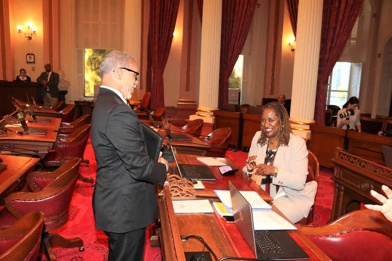 CDU President David Carlisle greets Senator Holly Mitchell at her esteemed place on the floor of the Senate.