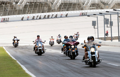 Some of the motorcycle riders coming down Pit Road after their trip around the race track.