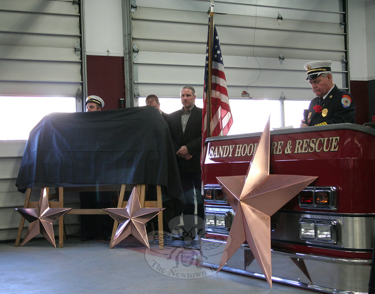 Anthony Capozziello, Jeff Gazerro and Greg Gnandt prepared to unveil the plaque; at the podium is Sandy Hook Chief William Halstead.