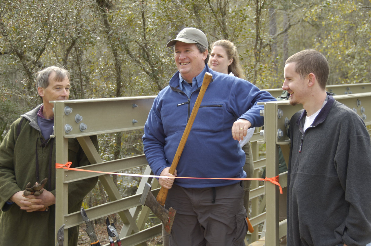 L to R: Ian Barlow, Kent Wimmer, Michelle Mitchell, and Judd Goodlin participate in the ribbon cutting on the Monkey Creek Bridge for the benefit of Robert Seidler's camera. PHOTO CREDIT:  Sandra Friend / Florida Trail Association