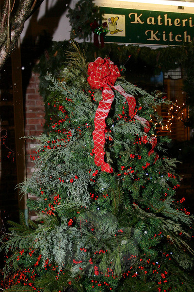 Pine, red ribbons and bows, and holly berries were placed around windows and on the islands in front of businesses in Sandy Hook Center in time for the Sandy Hook Tree Lighting on December 5.  (Hicks photo)