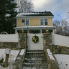 A gold bow on a green wreath at the gate of this Schoolhouse Hill Road complements the color of the home and the additional decorations that peek over the top of the gate.  (Hicks photo)