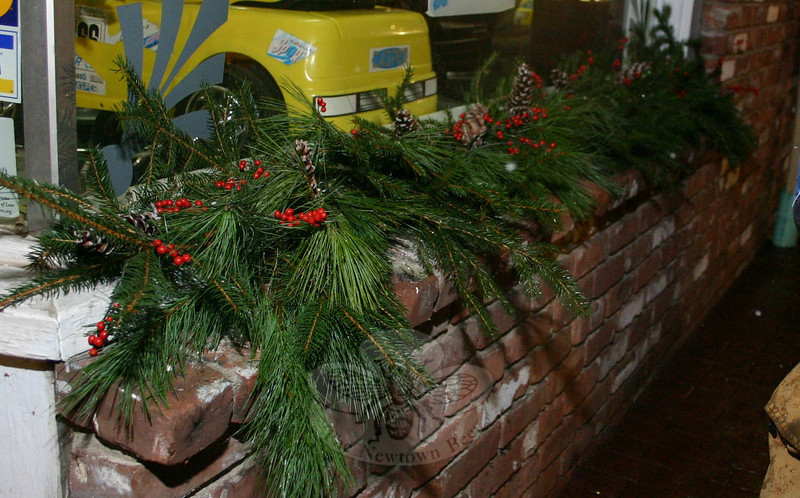 Pine roping and holly berries were placed around windows of businesses in Sandy Hook Center in time for this year's Sandy Hook Tree Lighting on December 5.  (Hicks photo)