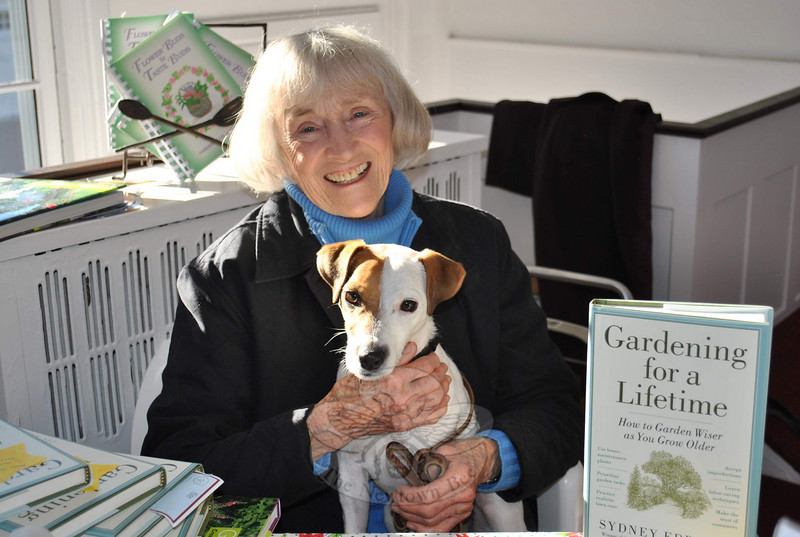 Garden expert and author Sydney Eddison, holding her Jack Russell terrier Phoebe, takes a break from autographing editions of her newest book, Gardening For A Lifetime, at the Garden Club of Newtown's Greenery Sale, Saturday, December 4, at Newtown Meeting House.  (Crevier photo)