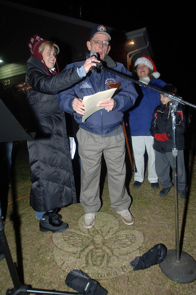 Hawleyville's inaugural tree lighting ceremony on Sunday, December 5, found residents gathered in the cold after 5 pm as longtime resident Edgar Beers offered his words and a brief local history before lighting the tree on the corner of Barnabas Road. One of the event's organizers, Ann Marie Mitchell, holds his microphone.  (Bobowick photo)