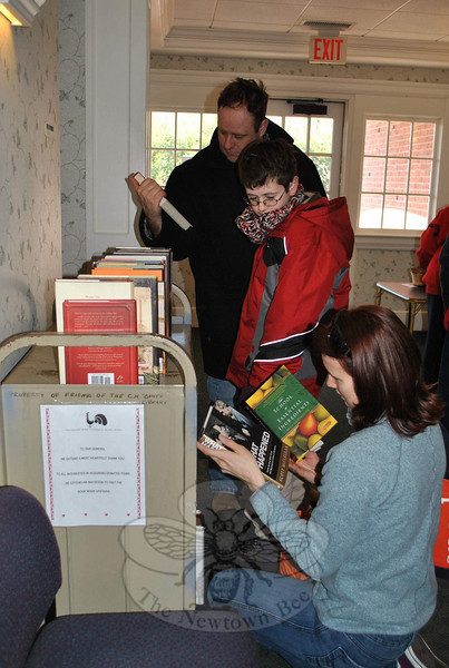 Kathryn Hanson kneels to get a closer look at some of the books offered at the Friends of the C.H. Booth Library Holiday Book Sale, Saturday, December 4, while Patrick McCleary and his son, Sean, look on.  (Crevier photo)