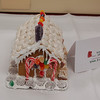 """Victoria Weimann won the First Place Individual Grade 3-5 in the Holiday Festival Gingerbread House Contest. Her tidy gingerbread cottage featured a """"stained glass"""" window made of gumdrops, frosted cookie shingles, and chocolate bar shutters.  (Crevier photo)"""