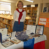 """Middle Gate second grade teacher Kristine Benton stands in the school's library with a display of her husband's memorabilia from his time in the Air Force. Donald Benton died while in service in 1985, and Mrs Benton said his collection was important to share with students for Veterans Day. """"I think today is a day when you really need to reflect on all that the military people give up in defense of their country,"""" she said. (Hallabeck photo)"""