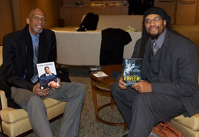 Kareem Abdul Jabbar & Etan Thomas - holding each others book.