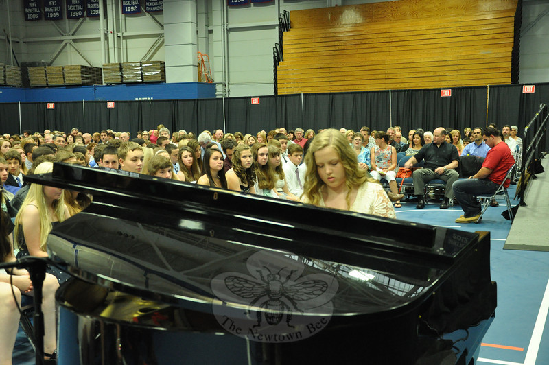 """NMS eighth grade student Aysha Hafiz played a rendition of Henry Mancini's """"Love Story"""" on a piano staged at the foot of the rostrum. Her inspired performance won a lengthy round of applause, which Aysha obliged with an modest curtsy before returning to her seat on the stage.   (Dietter photo)"""